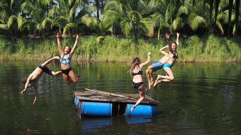 Students having fun in the swimming pond at Rak Tamachat Permaculture Thailand